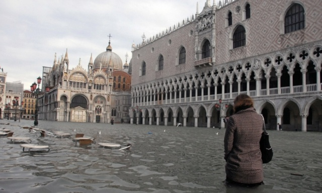 A woman walks through Piazza San Marco during a flood. Waters regularly rise above 130cm in the winter. Photograph: Andrea Pattaro/AFP/Getty